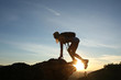 Woman tourist with backpack in tourist clothes climbs mountain. Silhouette against background sunrise