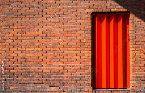 Grungy orange brick wall with a metal orange door with copy space Wallpaper Mural