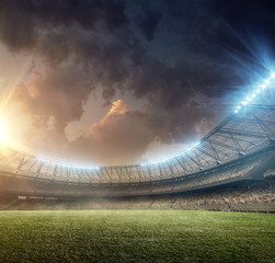 soccer stadium with illumination and green grass on sunset