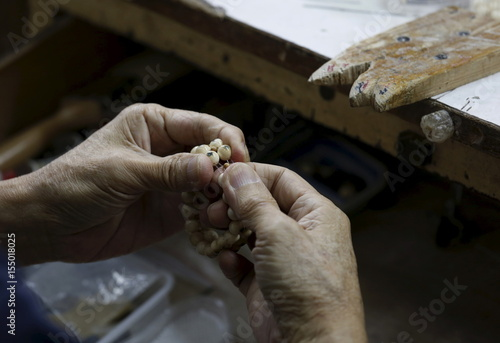A worker checks beads made from mammoth tusks inside a