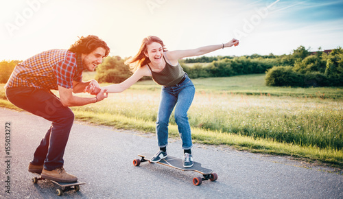 Fotografie, Obraz  Skateboarding couple having fun/ Couple enjoying and skateboarding at nature