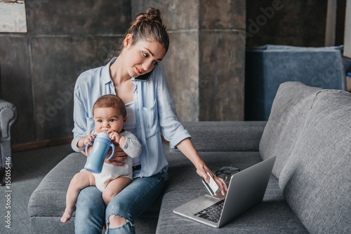 Fotografie, Obraz  Young mother with baby boy remote working and using laptop during conversation o