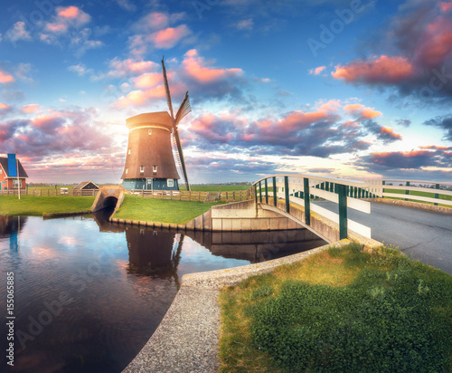 Poster Molens Windmill and bridge near the water canal at sunrise in Netherlands. Traditional dutch windmill and colorful blue sky in dusk. Summer rustic landscape in Holland. Sunny morning. Sky reflected in water