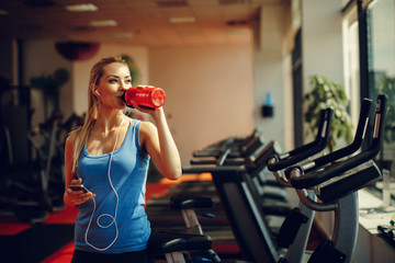 Fototapeta Beautiful young woman resting and drinking water in the gym