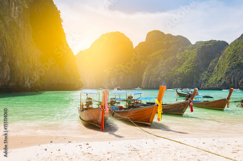 Traditional long tail boat docking in Maya bay in front of a clear and sandy bea Wallpaper Mural