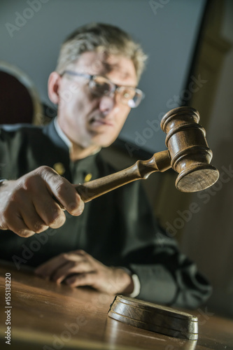 Fotografija  a judge with a hammer in his hand in the court room