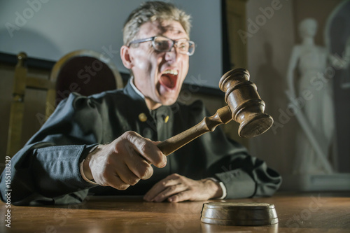 Valokuva angry man a judge with a hammer in his hand in the court room shouts and cry