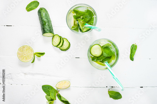 Spoed Foto op Canvas Opspattend water Cold and refreshing infused detox water with lime, mint and cucumber in a glass on wood background