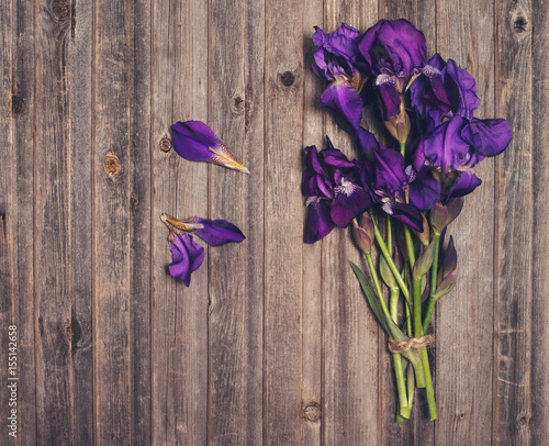 Purple iris flowers bouquet on weathered wooden background. Retro styled floral texture.