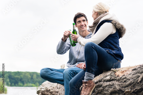 Fotografia Young couple, woman and man, sitting on tree stump at the riverside drinking bee