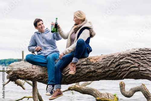 Fotografia, Obraz Young couple, woman and man, sitting on tree stump at the riverside drinking bee