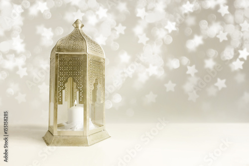 Ornamental golden Arabic lantern on the table with glittering star-shaped bokeh lights. Greeting card for Muslim community holy month Ramadan Kareem. Festive blurred background with empty space.