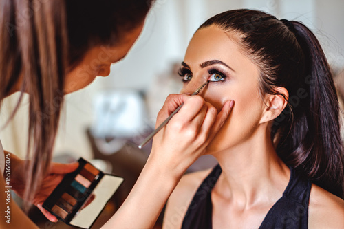 Makeup artist applying eyeshadow on a girl