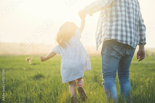 father and child walking on sunset