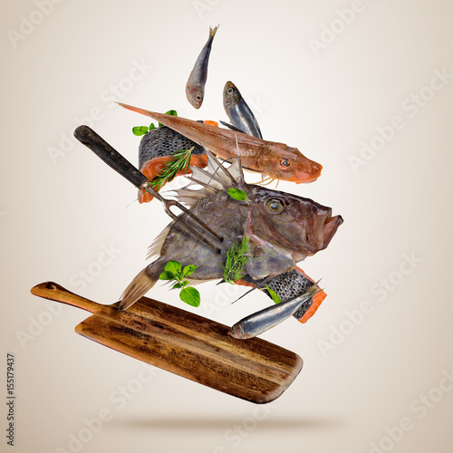 Fresh sea fish with falling spices, flying above wooden board Canvas Print