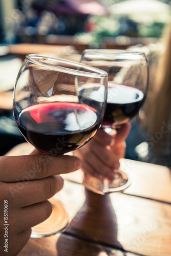 Poster de jardin Bar Young couple with glasses of red wine in a restaurant with city view
