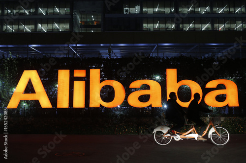 a77d49f4a2cd1e People ride a double bicycle past a logo of The Alibaba Group at the  company s headquarters on the outskirts of Hangzhou