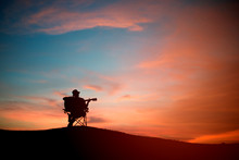 Silhouette Of Asia Young Man With Playibg Acoustic Guitar, Sunset Background