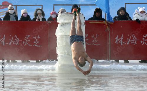 A man dives backwards off a ice block into a pool carved out of the