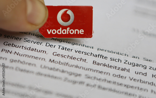 A SIM card of Vodafone is pictured in front of a letter of
