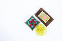 Spa Decorate Background Concept, Natural Hand Soap Bar And Rose Incense Cone On Green Ceramic Plate And Yellow Rose Candle On White Background