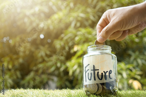 Fototapeta Money saving, Hand putting coin in glass jar with coins inside For now and future money. Concept of saving money for future. obraz