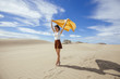 Woman in sand dunes waving a yellow sarong in a beautiful sunny day