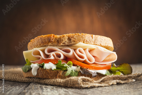 Staande foto Snack Tasty sandwich with ham, cheese, tomato and lettuce on wooden background