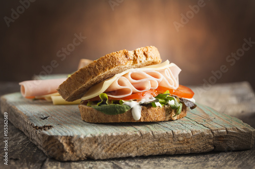 Fotobehang Snack Tasty sandwich with ham, cheese, tomato and lettuce on wooden background
