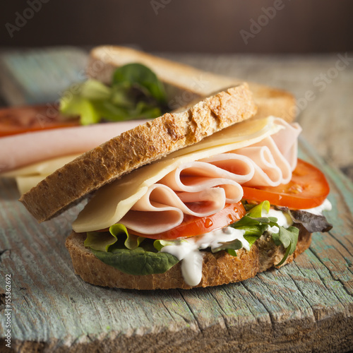 Keuken foto achterwand Snack Tasty sandwich with ham, cheese, tomato and lettuce on wooden background