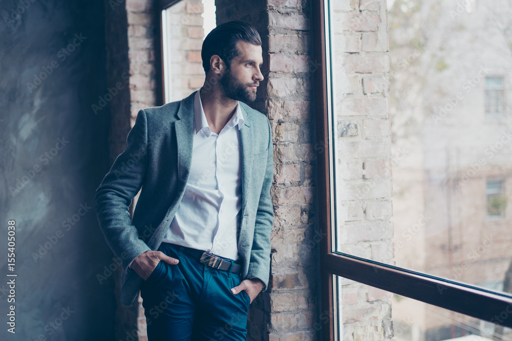 Fototapety, obrazy: Success concept. Stylish young bearded man is standing near the window and looking far. He is in a suit and, with hands in pockets, pensive and concentrated