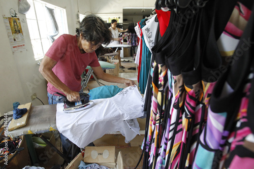 A garment worker irons a newly sewn maternity dress at a