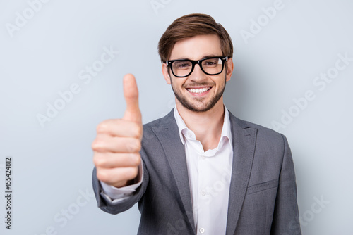 Fotomural  Successful excited bearded young guy in glasses and formal wear is standing isol