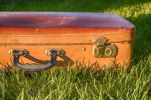 Papiers peints Retro Vintage antique suitcase, pen and lock close-up on a background of green grass travel concept