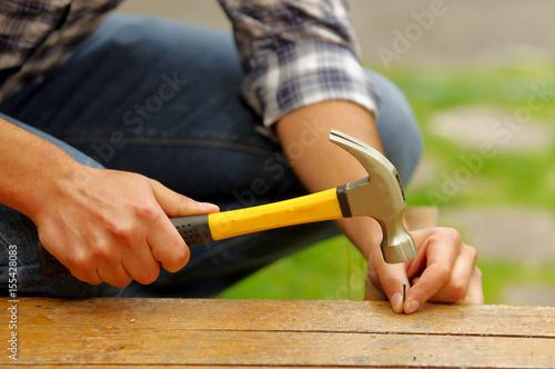 Fotografie, Obraz Casual man hammering nail in plank at home
