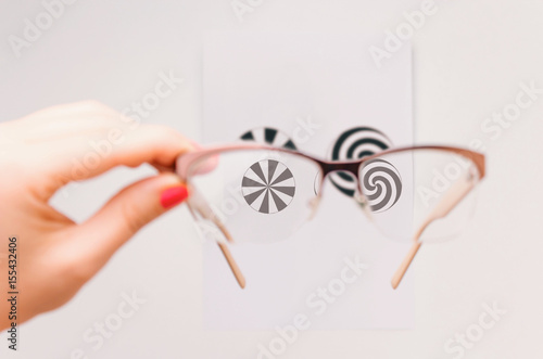 Photo Woman's hand holding eyeglasses and checking for astigmatism