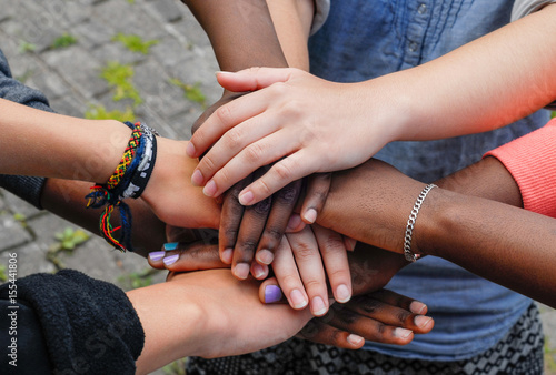 Photo  Multiracial teenagers joining hands together in cooperation