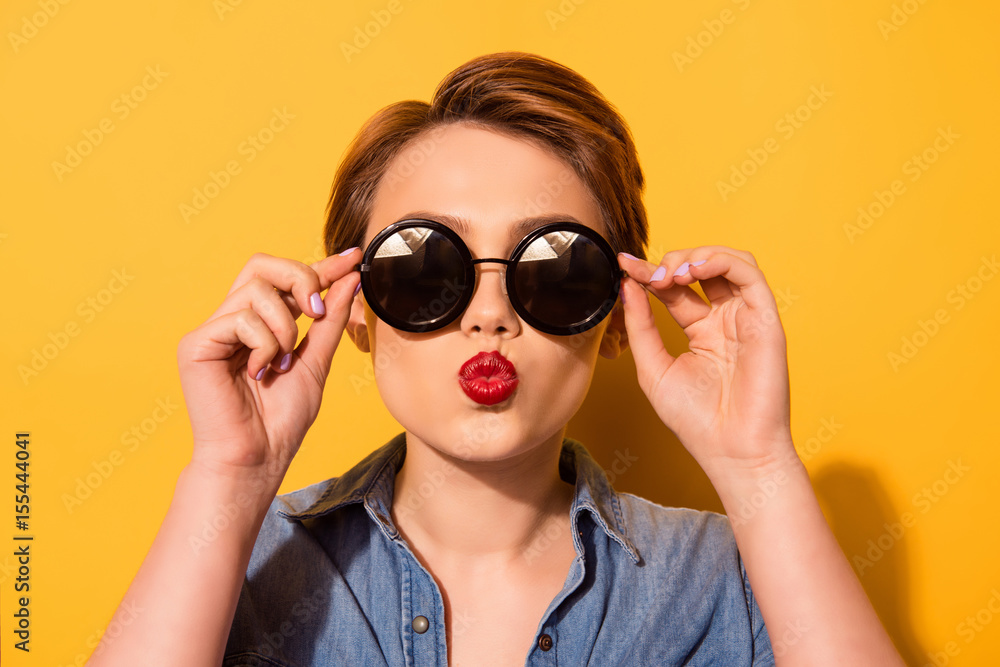 Fototapeta Kiss for you! Fashionable young cute girl in trendy sunglasses sends a kiss against bright yellow background, she holds spectacles with her hands