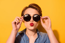 Kiss For You! Fashionable Young Cute Girl In Trendy Sunglasses Sends A Kiss Against Bright Yellow Background, She Holds Spectacles With Her Hands