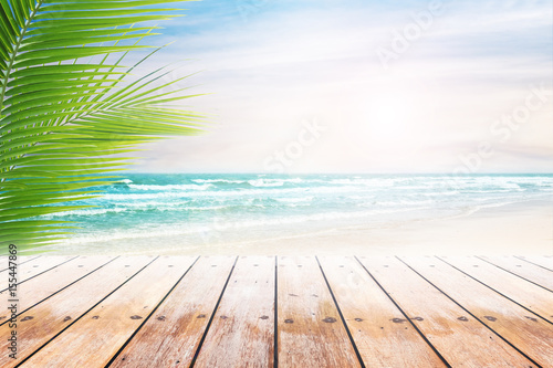 Foto auf Gartenposter Strand Empty wooden table and palm leaves with party on beach blurred background. Concept Summer, Beach, Sea, Relax, Party.
