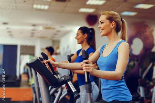 Poster Fitness Two young woman exercising on stepper machine at gym