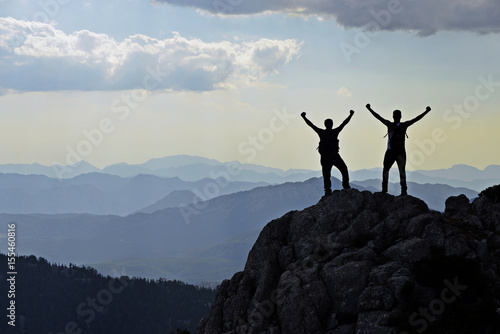 Photo  Two friendly adventurers on mountain tops
