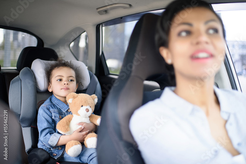 Photo portrait of mother and little daughter driving in car together