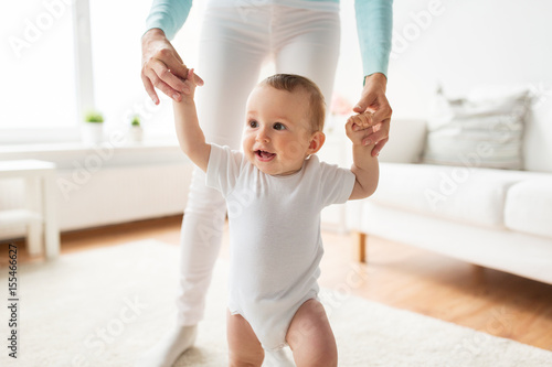 Photo  happy baby learning to walk with mother help