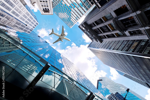 Airplane flying over business skyscrapers Fototapeta