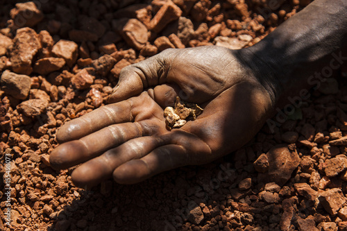 An artisan miner displays raw gold nuggets at an excavation