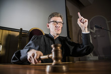 A Judge With A Hammer In His H...