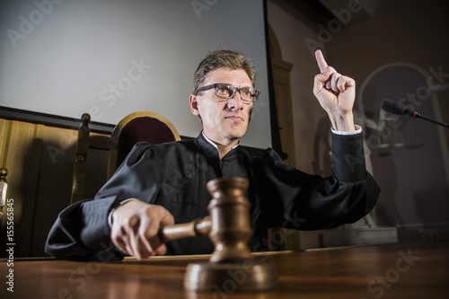a judge with a hammer in his hand in the court room Canvas Print