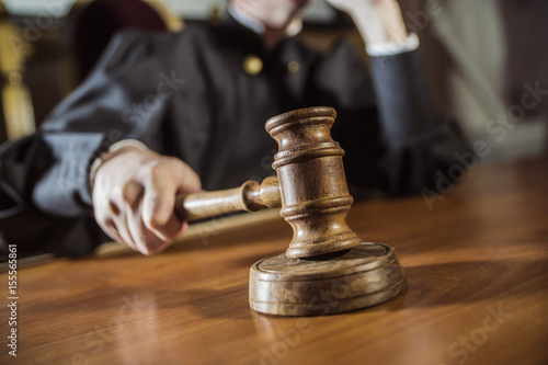 Fotografering  the hammer in the hand of the judge