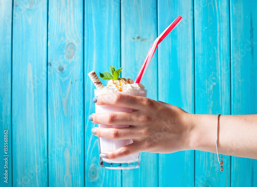 Tuinposter Milkshake Woman hand and Homemade milkshake with caramel on blue wooden table
